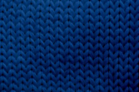 Classic blue tone texture knitted scarf with place for text. Close up trendy 2020 color