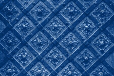 Old texture cathedral metal door in detail. Background Classic blue toning trend 2020