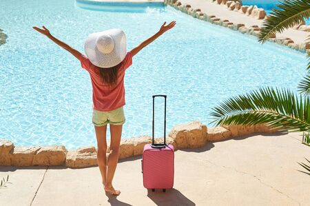 Travel, summer holidays and vacation concept - Beautiful woman raises her hands up near hotel pool area with pink suitcase