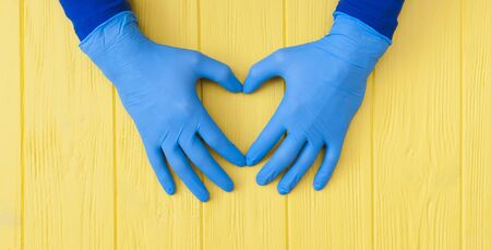 Blue Nitrile gloves. Hands of a medic in the blue latex gloves on yellow wooden table banner Stock Photo