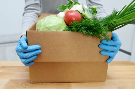 Volunteer in gloves holds food donation box vegetables to help the poor. Donat box with foodstuffs Reklamní fotografie