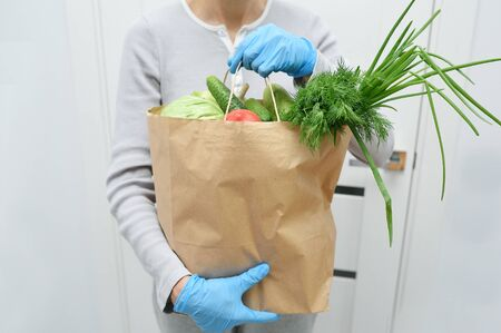 Volunteer in blue gloves holds food donation package vegetables to help the poor. Donat box with foodstuffs Reklamní fotografie
