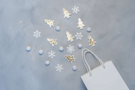 Christmas mockup shopping concept. Kraft white package with snowflakes and fir tree with place for your text on gray background. New Year flat lay mock up. Top view Foto de archivo - 160774244
