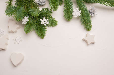 Christmas composition with green fir branches and white wooden decorations of stars and hearts on white wooden background with copyspace