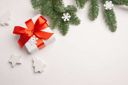 Christmas composition with green fir branches and white gift box, stars and snowflakes on white wooden background, with copyspace Foto de archivo - 160774246