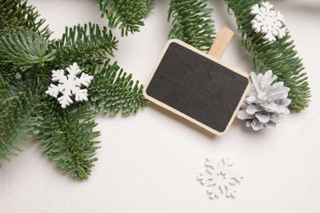 Christmas composition with green fir branches, cone and white wooden decorations of snowflakes on white wooden background, with copyspace Foto de archivo - 160761081