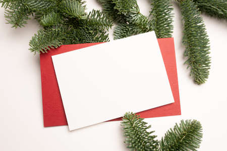 Christmas greeting card with envelope on wooden white background with fir tree branches and happy new year decorations. Top view copyspace Foto de archivo - 160760947
