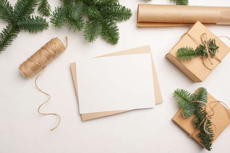 Christmas mockup greeting card with envelope on wooden white background with fir tree branches and happy new year decorations. Top view copyspace