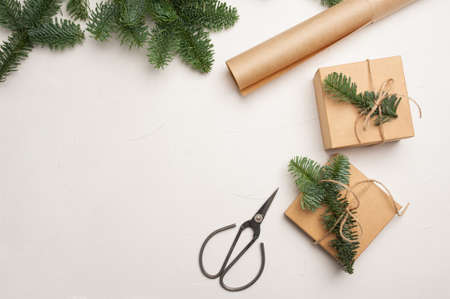 Christmas composition with green fir branches and kraft paper gift boxes and scissors on white background, Top view with copyspace Foto de archivo - 160774248