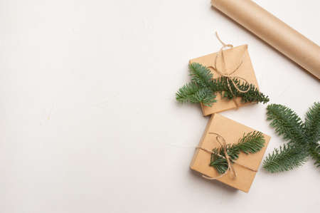 Christmas composition with green fir branches and kraft paper gift boxes on white background, Top view with copyspace