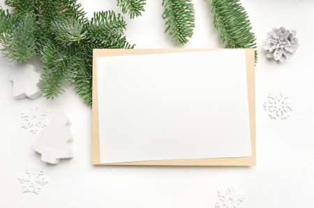 Mockup Christmas greeting card with envelope on wooden white background with fir tree branches and happy new year decorations. Top view copyspace Foto de archivo - 161618506