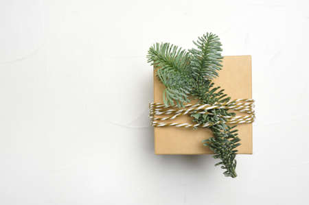 Christmas composition with green fir branches and kraft gift box on white wooden background with copyspace Foto de archivo - 161618514