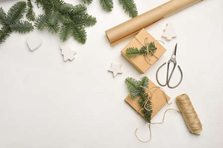 Christmas composition with green fir branches and kraft paper gift boxes and scissors on white background, Top view with copyspace