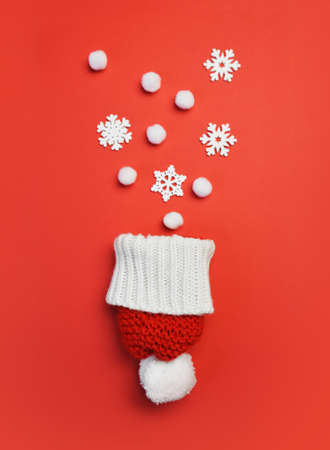 Christmas greeting card with red hat and snowflakes on red backgroun. Xmas holiday postcard with place for your text. Happy New Year winter Foto de archivo - 161618517