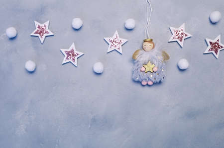 New Year or Christmas background. wooden gray background with winter angels, stars and small snowflakes. With place for your text, top view, copy space