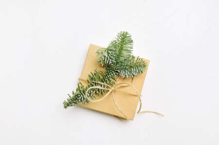 Christmas composition with green fir branches and kraft gift box on white wooden background with copyspace Foto de archivo - 161562085