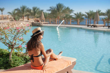 Woman in a straw hat relaxing on a daybed near a luxurious summer pool hotel Egypt, concept time to travel Foto de archivo