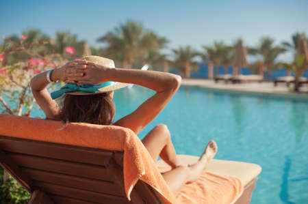 Woman in a straw hat relaxing on a daybed near a luxurious summer pool hotel Egypt, concept time to travel Foto de archivo - 162528699