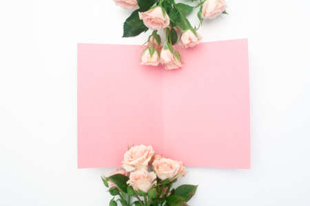 wedding or birthday mock up scene. Blank open sheet of paper with place for text for greeting card. Bouquet of pink roses on white background. Flat lay, top view
