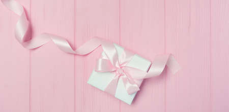 Banner Gift box with ribbon on pink wooden background with place for your text. Mock up on Valentines Day, mothers day or Birthday. Top view, flat lay Foto de archivo - 162528739