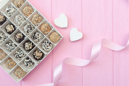 Chocolate handmade candies on pink wooden table. Chocolate box open with two hearts and a festive ribbon. Gift for valentines day Foto de archivo