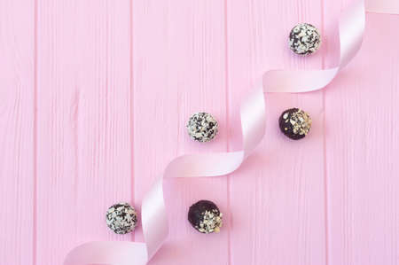 Chocolate handmade candies on pink wooden table with festive ribbon with place for your text copyspace Foto de archivo - 162594894