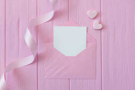 Wedding or birthday mock up scene. Blank open envelope with place for text for greeting card copyspace. Valentines card with two hearts on pink background. Flat lay, top view