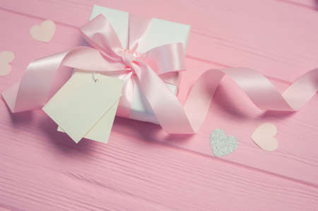 White gift box with a pink satin bow and ribbon on pink wooden background. Wedding mockup tag is included for your text. Can use for Valentines Day, mothers day, birthday Foto de archivo - 162594900