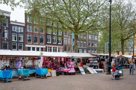 AMSTERDAM, NETHERLANDS. JUNE 06, 2021. Beautiful view of Amsterdam with typical dutch houses. Fair, market on the square Редакционное