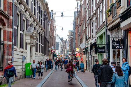 AMSTERDAM, NETHERLANDS. JUNE 06, 2021. Beautiful view of Amsterdam with typical dutch houses. Shops on the street.