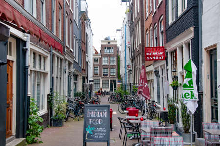 AMSTERDAM, NETHERLANDS. JUNE 06, 2021. Beautiful view of Amsterdam with typical dutch houses. Small restaurants on the street. Редакционное