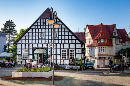 BUNDE, GERMANY. JUNE 12, 2021. DeLaCasa restaurant on the square, pink bicycle before the entrance with advertizing of apiary Land Frauen. Beautiful view of small german town with typical architecture. Fachwerk style, Prussian wall. Редакционное