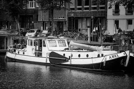 AMSTERDAM, NETHERLANDS. JUNE 06, 2021. Beautiful view of Amsterdam with typical dutch houses, bridges and chanel. Small boats on the embankment. Black and white photography.