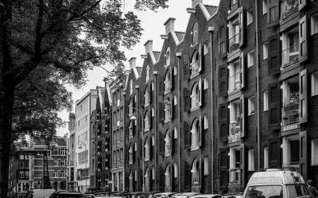 AMSTERDAM, NETHERLANDS. JUNE 06, 2021. Beautiful facades of the old dutch buildings. House with a names of the Citiyes on the balcony. Black and white photography.