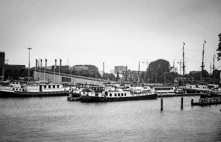 AMSTERDAM, NETHERLANDS. JUNE 06, 2021. Beautiful view to a shipping channel and bridges. Black and white photography. Small boats, ships and barges in the port. Black and white photography. Редакционное