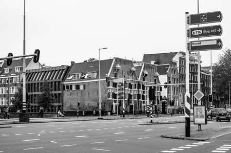 AMSTERDAM, NETHERLANDS. JUNE 06, 2021. Beautiful facades of the old dutch buildings. Restaurants on the street. Black and white photography.
