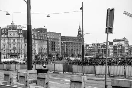 AMSTERDAM, NETHERLANDS. JUNE 06, 2021. Beautiful facade of the Victoria Hotel on the background, old dutch buildings. Black and white photography.