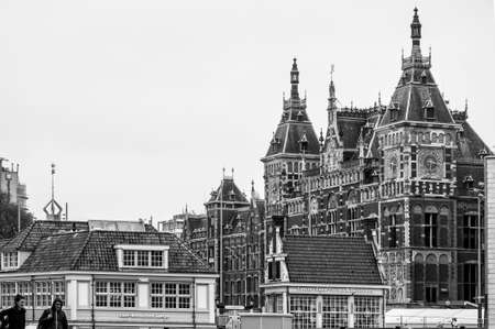 AMSTERDAM, NETHERLANDS. JUNE 06, 2021. Beautiful facade of Amsterdam Vity Center on the background, old dutch buildings. Black and white photography.