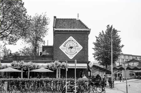 AMSTERDAM, NETHERLANDS. JUNE 06, 2021. Brewery IJ next to De Gooyer windmill. Black and white photography.
