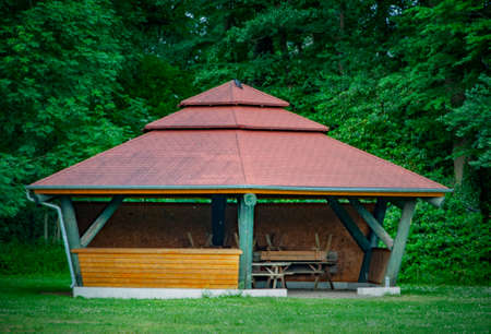VERSMOLD, GERMANY. JUNE 20, 2021 Campingpark Sonnensee. Wooden gazebo in a country style on a green meadow. People resting in the forest.