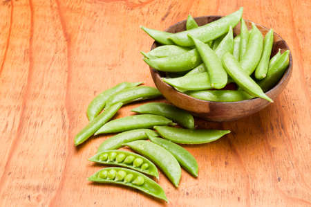 Fresh snap peas in a wooden bowl on a wooden table photo