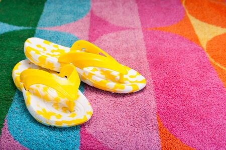 Bright yellow flip-flops on a colorful beach towel photo