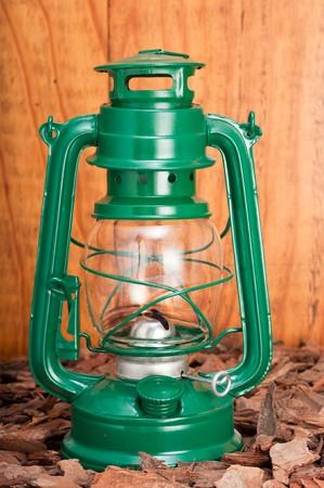 oillamp: Green lantern on bark chips against wooden background