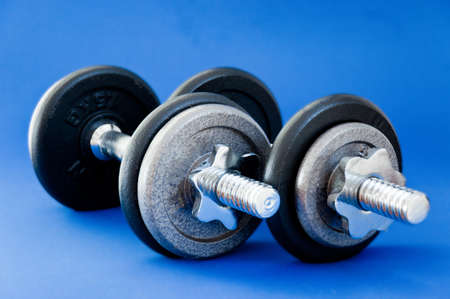 A pair of barbells on a blue background Stock Photo - 8594371