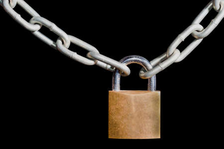 galvanised: Brass padlock and locked onto a heavy galvanised chain, isolated on a black background Stock Photo