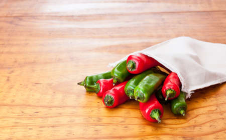 Fresh green and red chilli peppers in a cloth bag, displayed on a beautiful wooden table photo