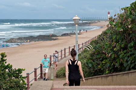 locals: DURBAN, SOUTH AFRICA - JULY 09, 2016: Locals and tourists on the promenade near the Millennium Pier in Umhlanga Rocks Editorial
