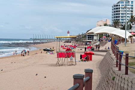 DURBAN, SOUTH AFRICA - JULY 09, 2016: Locals and tourists on the beach near the Millennium Pier and lighthouse in Umhlanga Rocks