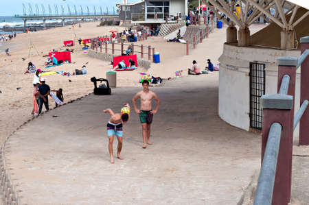 locals: DURBAN, SOUTH AFRICA - JULY 09, 2016: Locals and tourists on the beach near the Millennium Pier and lighthouse in Umhlanga Rocks