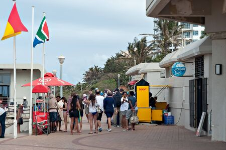 locals: DURBAN, SOUTH AFRICA - JULY 09, 2016: Locals and tourists on the promenade near the Millennium Pier and lighthouse at Umhlanga Rocks beach